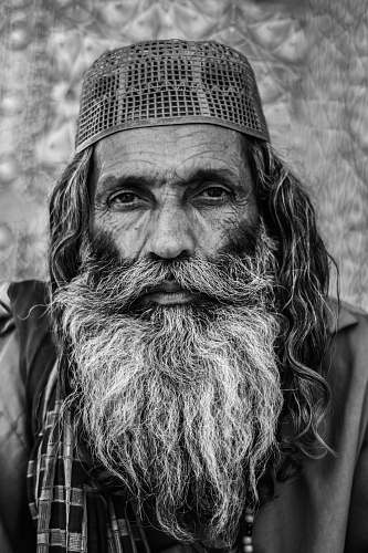 portrait grayscale photo of man in cap beard