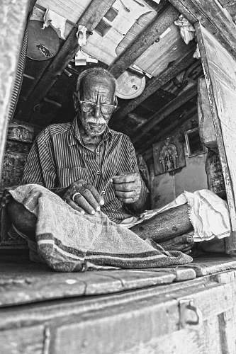 people grayscale photo of man sewing textile while sitting on floor india