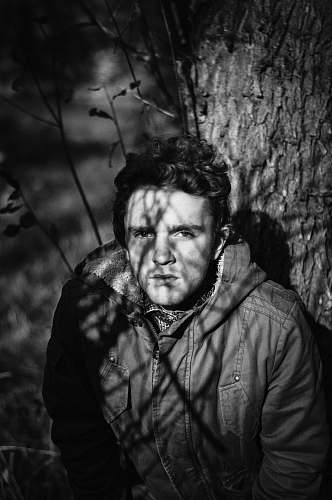 people grayscale photo of man under tree person