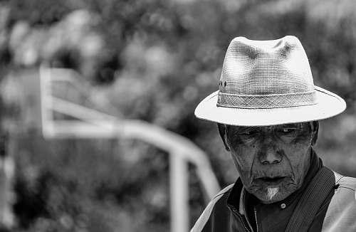 portrait grayscale photo of man wearing hat tibet