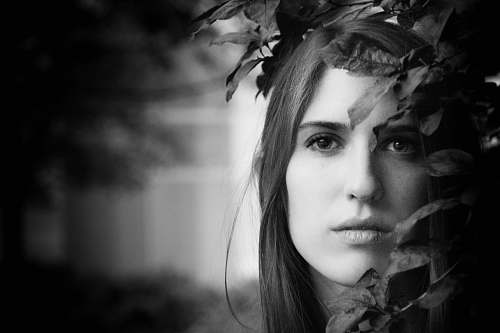 portrait grayscale photo of woman beside leaves female