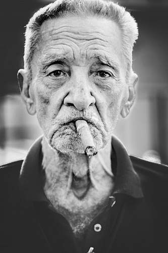 people grayscale photography of man smoking cigar person