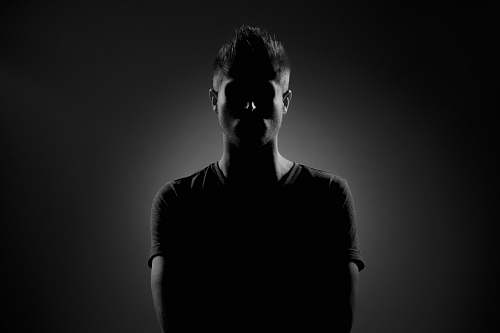 person grayscale photography of man wearing black t-shirt human