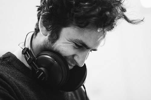 human grayscale photography of man with headphones on neck headphones