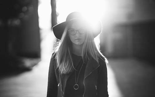 human grayscale photography of woman wearing hat and coat standing near wall female