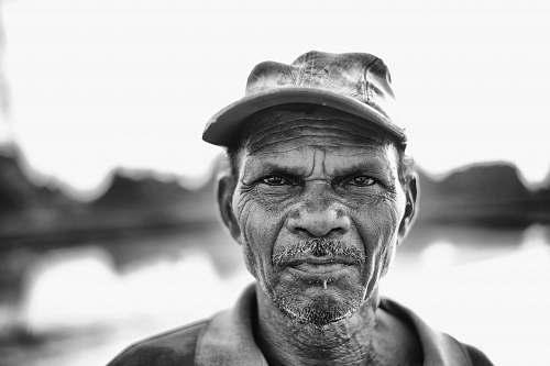 human man wearing cap near body of water during daytime portrait