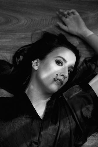 people grayscale photography of woman lying on wooden surface black-and-white
