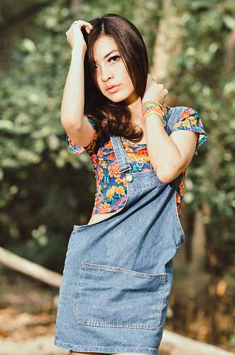person shallow focus photography of woman wearing blue, yellow, and red floral top posing near trees people