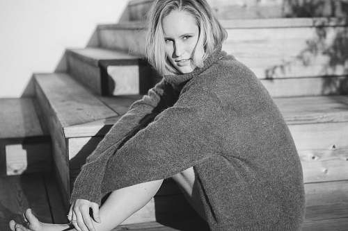 person woman wearing cardigan sitting on stairs black-and-white