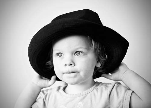 human grayscale photography of girl with hat black-and-white