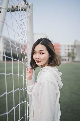 woman man in white pullover hoodie standing beside white goal net girl
