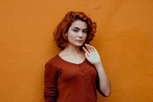 person woman in red button-up shirt leaning orange wall human