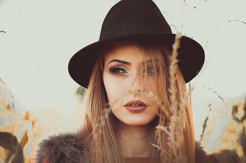 person woman wearing black hat standing beside beige grass hat