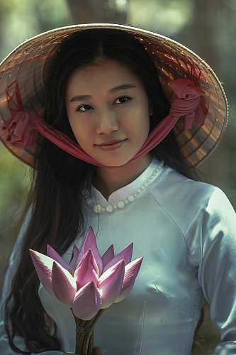 woman woman wearing white long-sleeved dress and brown sungat holding pink petaled flower female