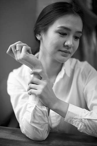 human woman holding her forearm black-and-white