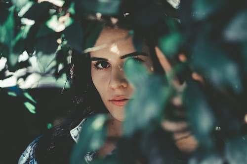 human woman wearing blue denim top hiding beside grasses people