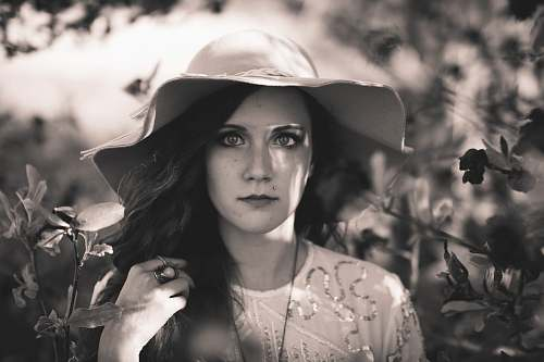person grayscale photography of woman wearing sun hat human