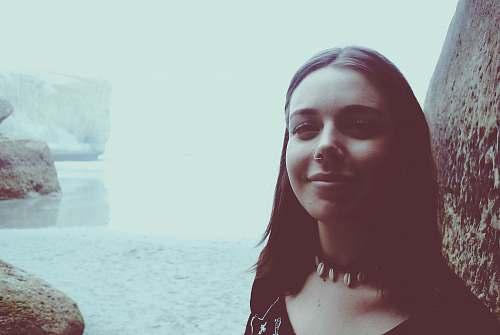 female woman taking selfie near body of water and rocks new zealand