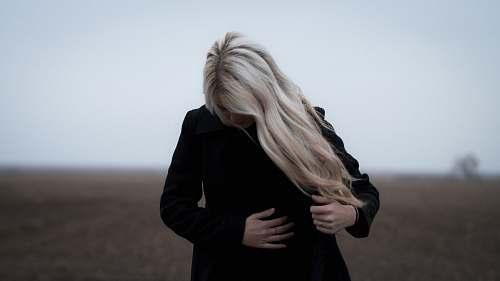 female woman wearing black coat blonde