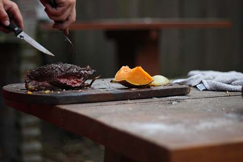 photo food person slicing a meat using knife and fork bbq free for commercial use images