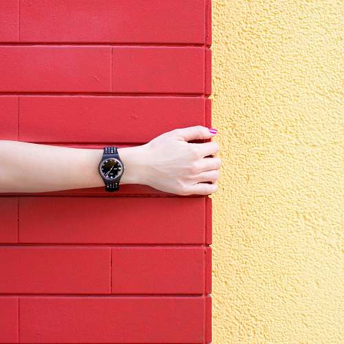 barrio chino person wearing black analog watch holding red brick wall forearm