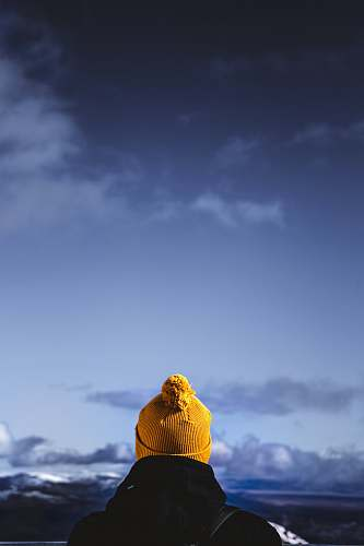 photo hat person wearing brown bobble hat facing cloudy skies buddha free for commercial use images