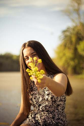 photo person woman holding yellow flower during daytime human free for commercial use images