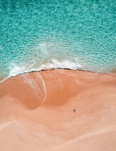 mexico aerial photography of two person sunbathing on seashore blue