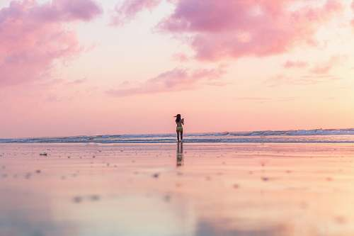 ocean woman standing on seashore in front of body of water coast