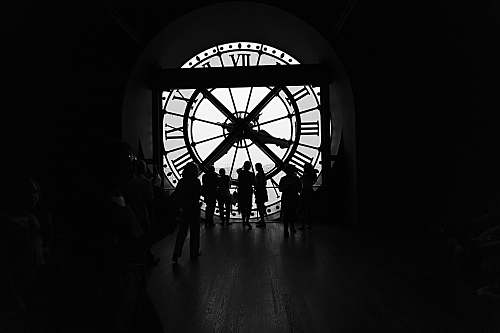 person silhouette of people across large clock human