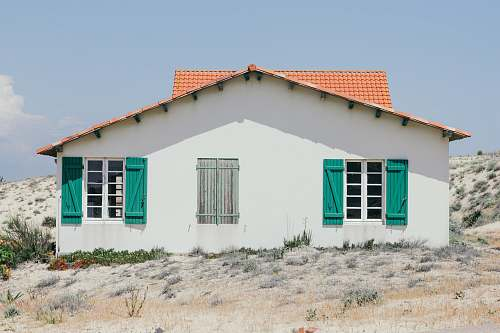 france white and green concrete house with windows open at daytime house