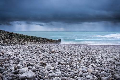 photo waves body of water across pebbles under dark sky pebble free for commercial use images