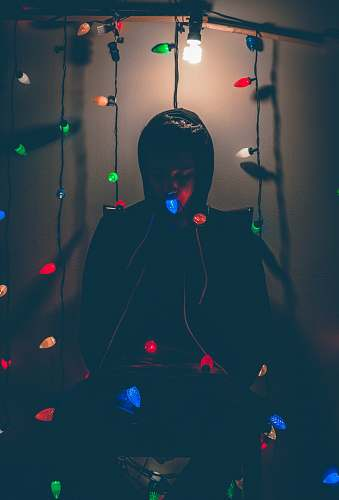 photo paper man sitting while biting multicolored string lights edinburg free for commercial use images