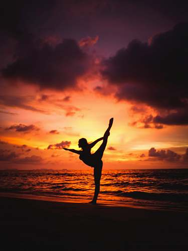 sport silhouette photography of woman stretching front of sea yoga
