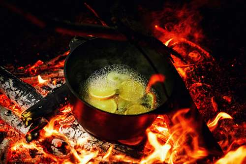 flame dutch oven on lit firewood with water and slices of fruits bonfire