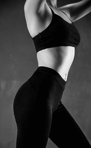 human grayscale photo of person wearing sports bra and leggings black-and-white