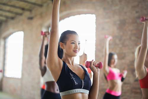 person women doing exercise raising left hands while holding dumbbells inside room people