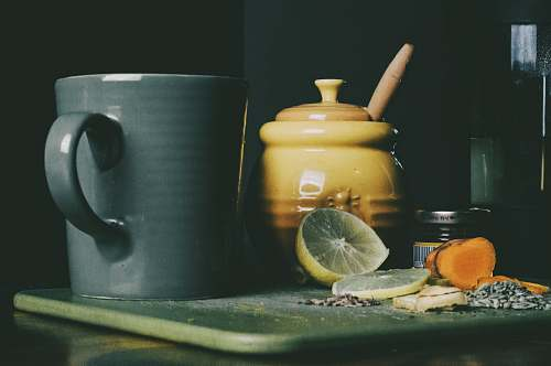 person beige ceramic jar beside grey ceramic pitcher and sliced lemon fruit cup