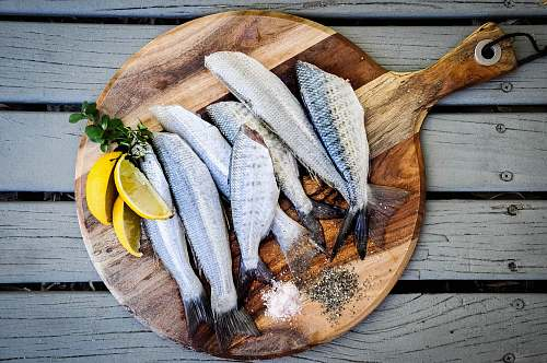 photo fish headless fishes with sliced of lemons on brown wooden chopping board chopping board free for commercial use images