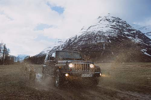 car photo of gray Jeep Cherokee near snow-covered mountain vehicle