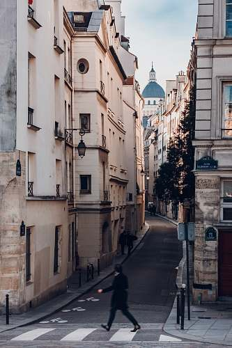 paris photography of person walking on sideway looking at leftside with buildings quai de la tournelle
