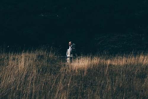 dark person on brown grass at daytime flora