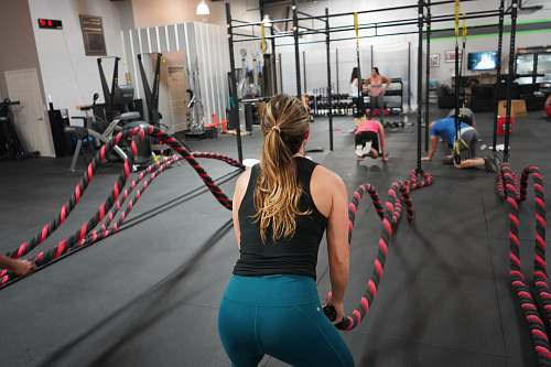 person woman in black top pulling rope working out