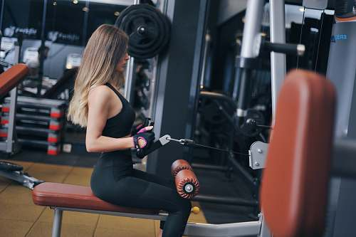 person woman sitting on exercise bench working out