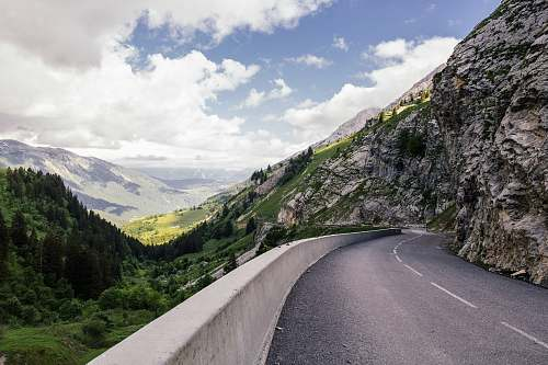 mountains curved road near cliff trees