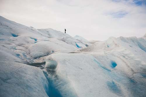 ice person standing on top of hill under white cloud blue skies glacier