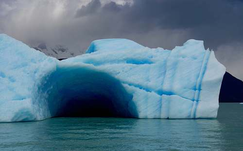 iceberg ice cave on top of body of water ice