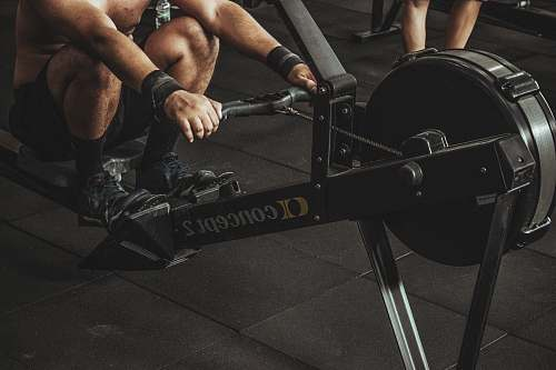 photo sport topless man using rowing machine exercise free for commercial use images