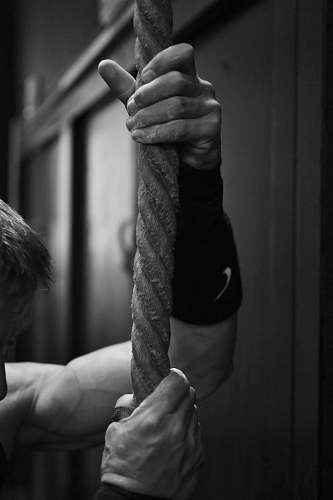 human gray scale photo of man holding rope black-and-white