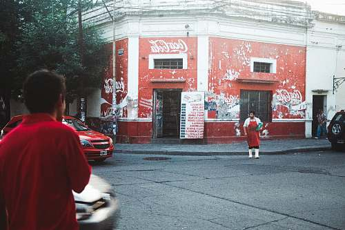 human man in red apron standing beside Coca-Cola building car